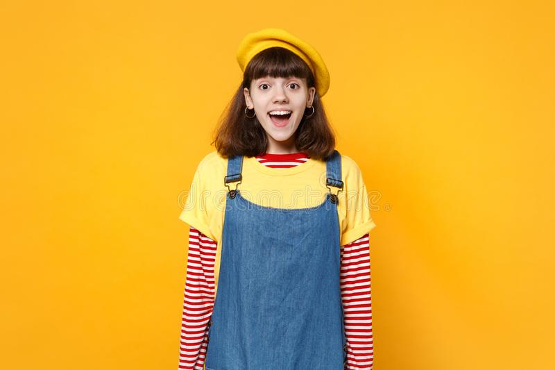 Portrait of excited cheerful funny girl teenager in french beret, denim sundress standing isolated on yellow wall stock photos