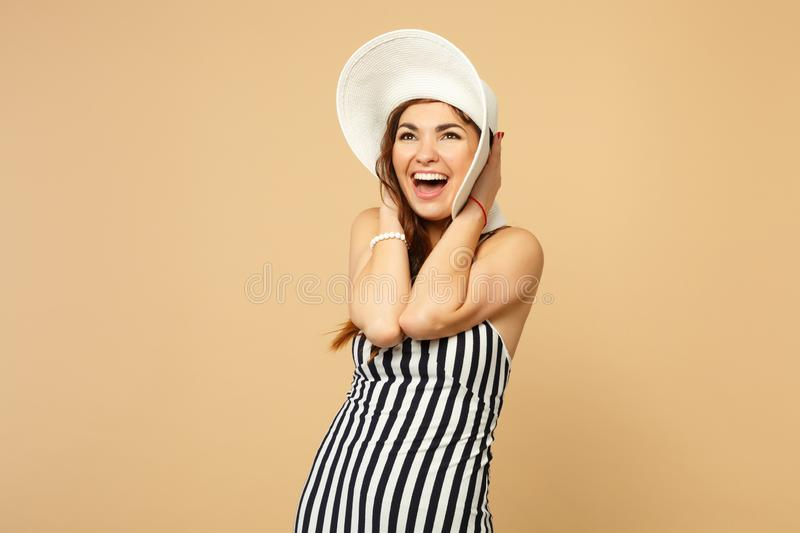 Portrait of excited cheerful woman in black and white striped dress, hat putting hand on head isolated on pastel beige royalty free stock photos