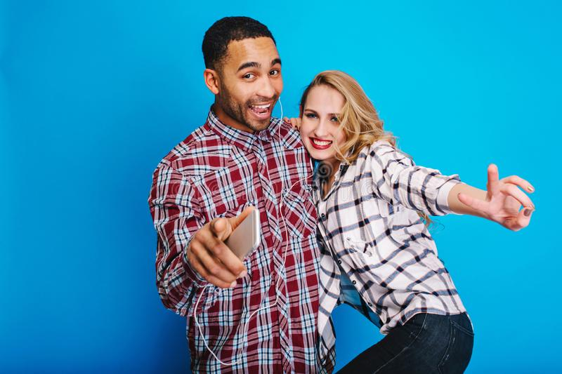 Portrait excited couple having fun together, listening to music through headphones on blue background. Stylish outlook stock photography