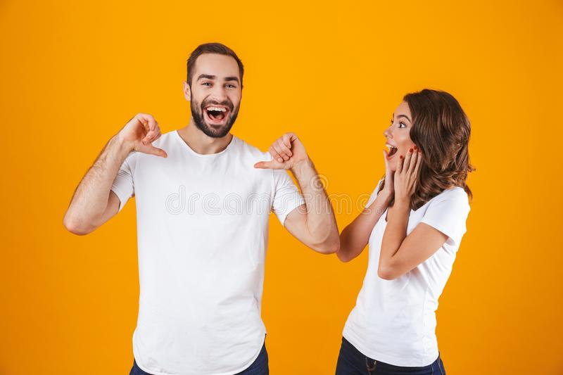 Portrait of excited couple man and woman in basic clothing pointing fingers, while standing together isolated over yellow. Portrait of excited couple men and royalty free stock photo