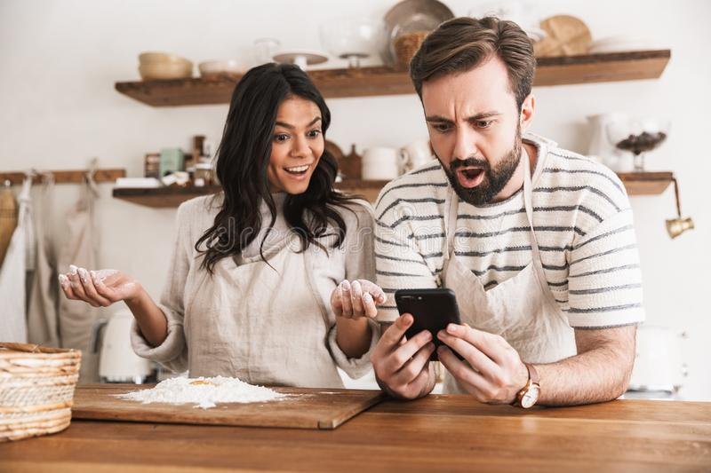 Portrait of excited couple reading recipe while cooking pastry with flour and eggs in kitchen at home stock image