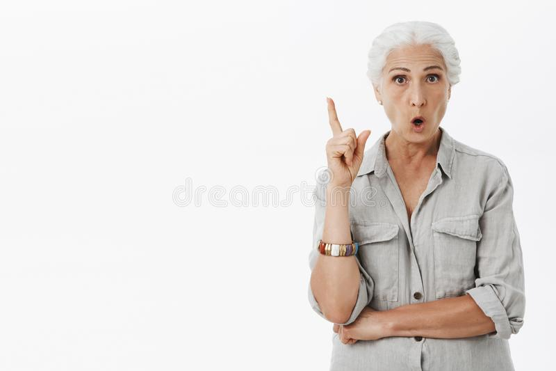 Portrait of excited creative and smart elderldy mother with white hair folding lips raising index finger in eureka. Gesture wanting add suggestion and tell part royalty free stock image