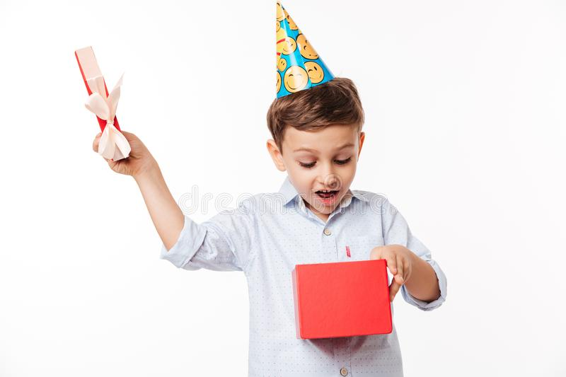 Portrait of an excited cute little kid in a birthday hat. Opening present box isolated over white background stock photos