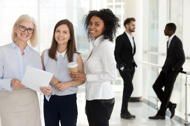 Portrait excited diverse female colleagues looking at camera in office stock photography