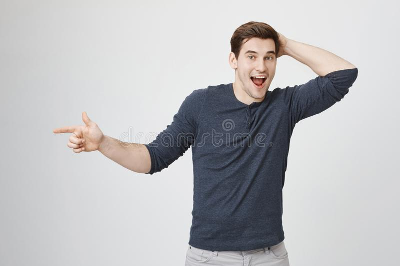 Portrait of excited european man pointing left with excited look and touching his head, standing over gray background royalty free stock image