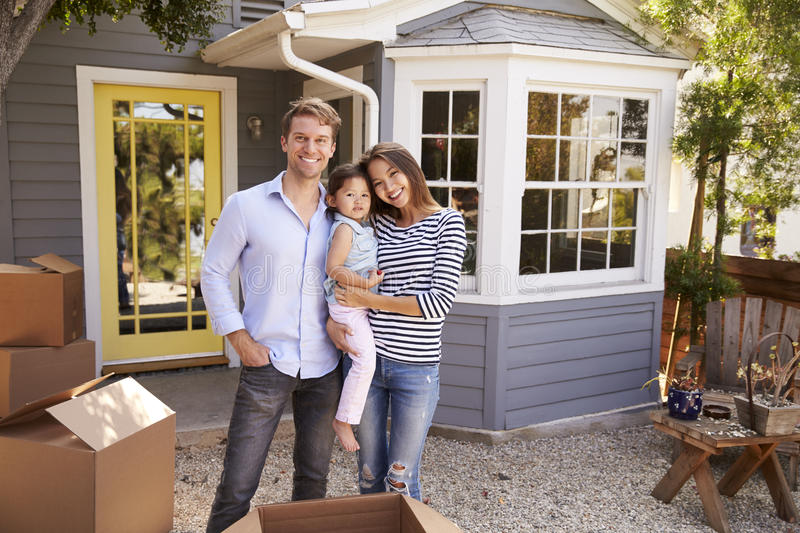 Portrait Of Excited Family Standing Outside New Home royalty free stock image