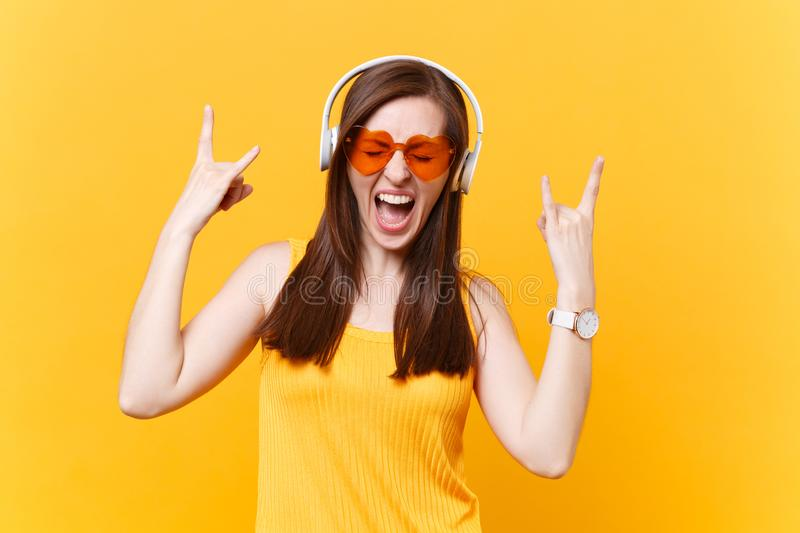 Portrait of excited fun girl in orange glasses listening music in headphones showing heavy metal rock sign, copy space stock photos