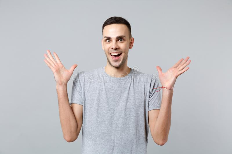 Portrait of excited funny young man in casual clothes keeping mouth open, spreading hands isolated on grey wall stock photography