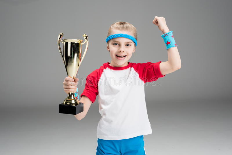 Portrait of excited girl holding champion`s goblet stock photography