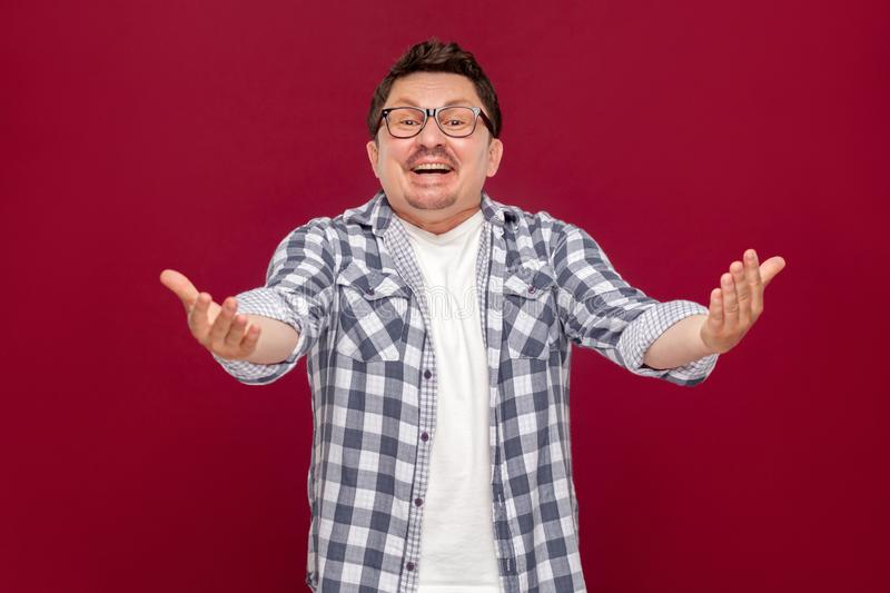 Portrait of excited handsome middle aged business man in casual checkered shirt, eyeglasses standing, toothy smile and looking at stock photos