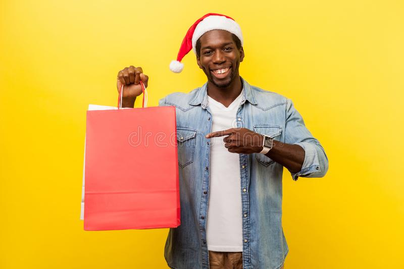 Portrait of excited handsome young man in santa hat and casual denim shirt standing pointing at shopping bag and looking at camera royalty free stock images