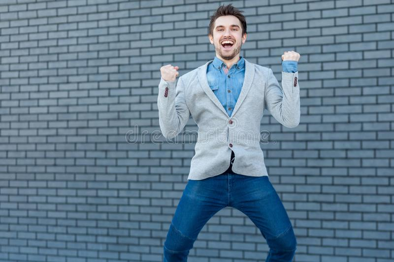 Portrait of excited happy handsome bearded man in casual style standing, jumping and looking at camera with happiness and stock photo