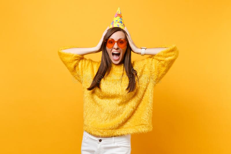 Portrait of excited joyful young woman in orange heart glasses and birthday party hat screaming, putting hands on head. Isolated on bright yellow background stock photos