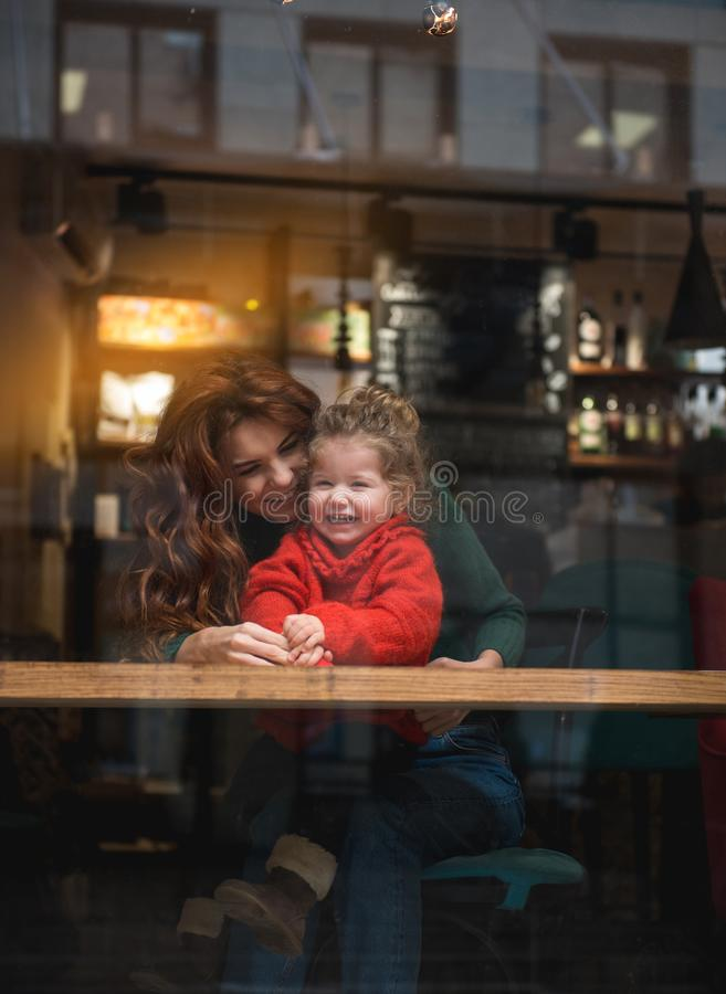 Joyful mom playing with her daughter in cafe royalty free stock photo