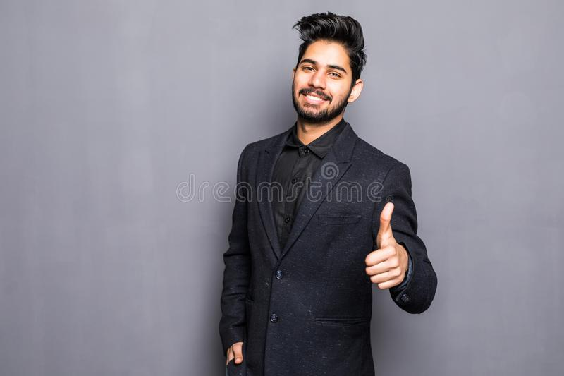 Portrait of excited indian man dressed in formal wear giving thumbs-up against gray background stock photo