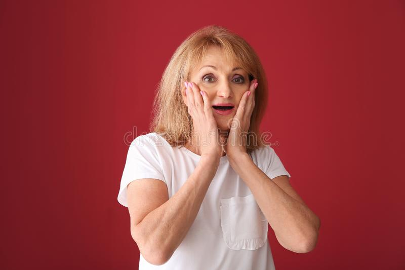 Portrait of excited mature woman on color background royalty free stock images
