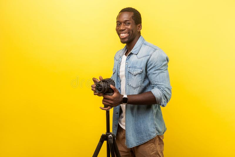 Portrait of excited motivated photographer posing professional digital dslr camera on tripod. studio shot isolated on yellow. Portrait of excited motivated royalty free stock image