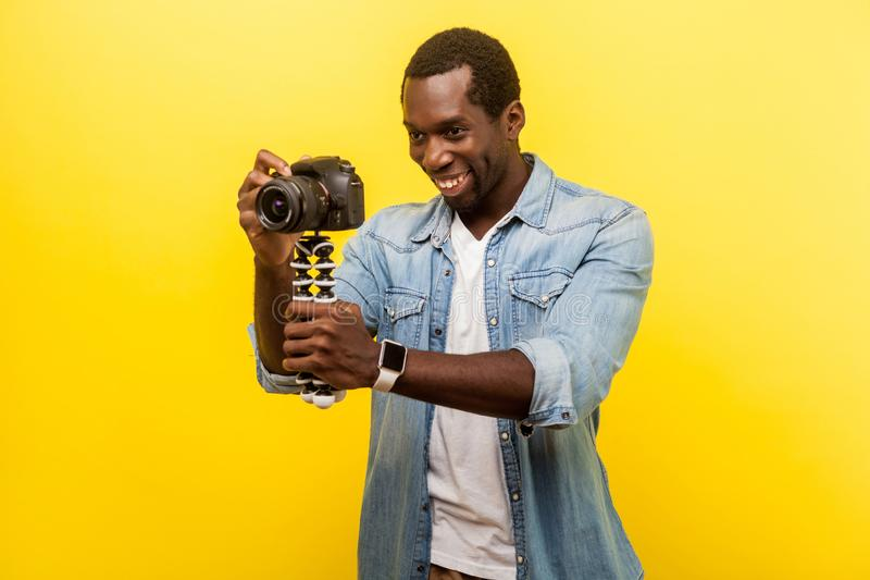 Portrait of excited photographer holding professional digital dslr camera. indoor studio shot isolated on yellow background. Portrait of excited photographer royalty free stock images