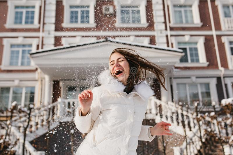 Portrait excited playful girl having fun with snow in frozen sunny morning on street. True emotions, laughing with. Closed eyes, brightful moments, christmas royalty free stock photography