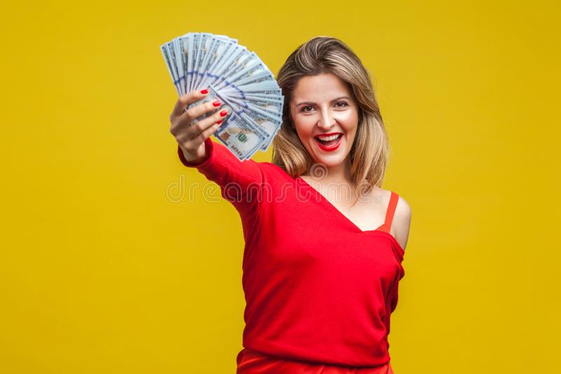 Portrait of excited rich beautiful woman in red dress holding money, isolated on yellow background stock photo