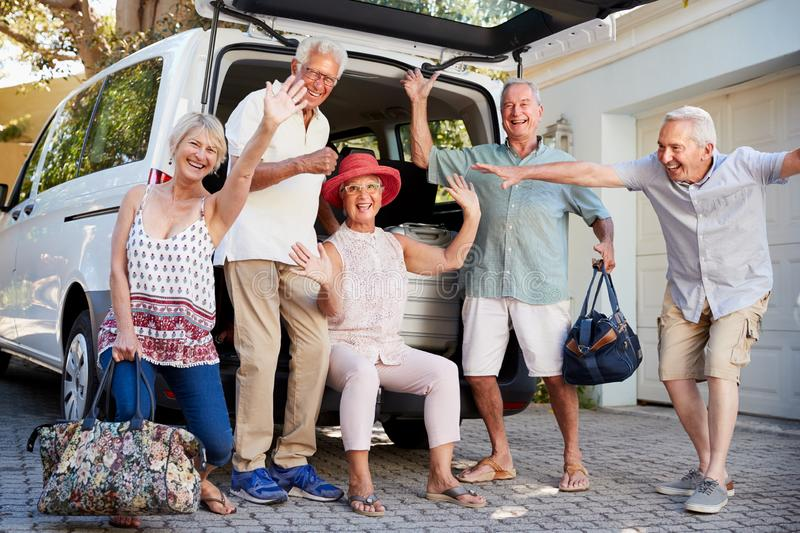 Portrait Of Excited Senior Friends Loading Luggage Into Trunk Of Car About To Leave For Vacation royalty free stock images