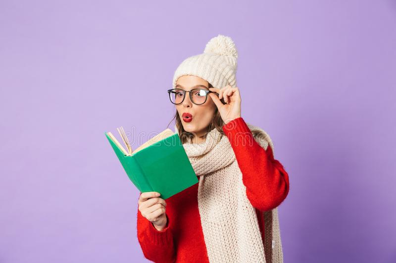 Young woman wearing winter hat isolated over purple background reading book. Portrait of an excited shocked young woman wearing winter hat isolated over purple royalty free stock image