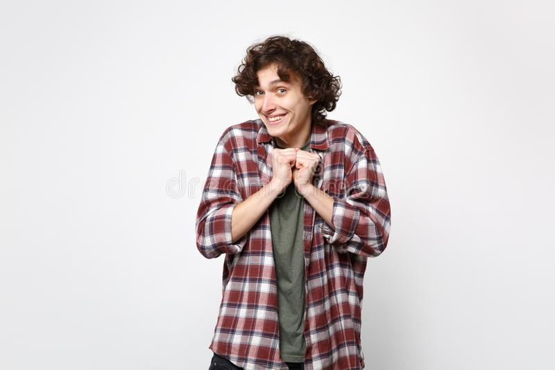 Portrait of excited smiling young man in casual clothes looking camera, clenching fists  on white wall royalty free stock image