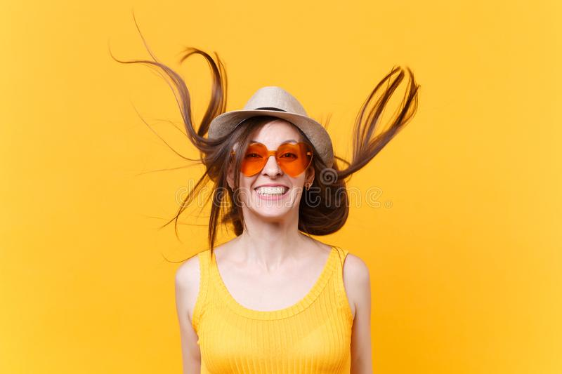 Portrait of excited smiling young woman in straw summer hat, orange glasses with fluttering hair copy space isolated on royalty free stock photography