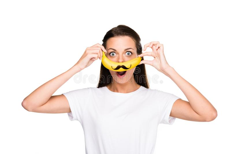 portrait of excited woman holding fresh banana with mustache sign stock photo