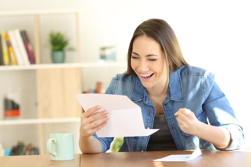 Excited woman reading good news in a letter royalty free stock photos