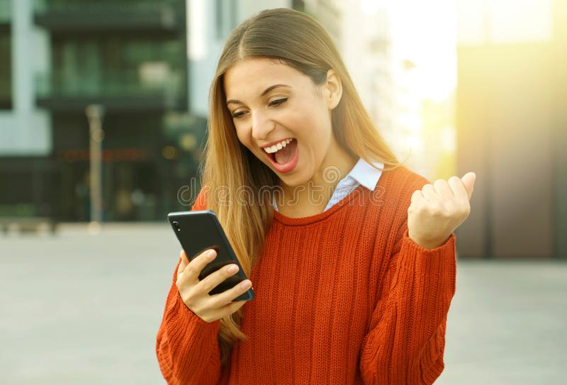 Portrait of an excited woman wearing a red sweater winning online outside on the street in autumn.  stock image