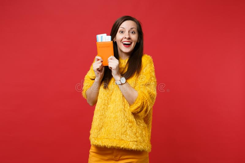 Portrait of excited woman in yellow fur sweater holding passport, boarding pass ticket isolated on bright red wall royalty free stock photos