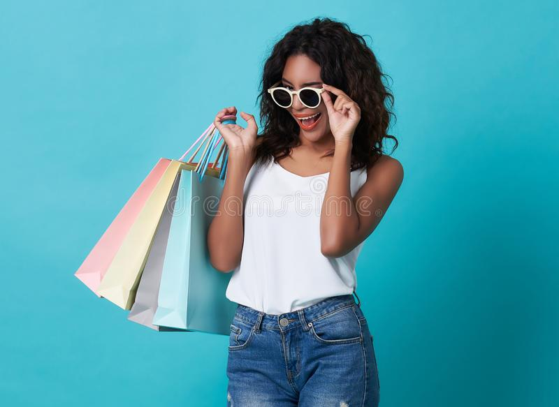 Portrait of an excited young african woman hand holding shopping bag and sunglasses isolated over blue background royalty free stock photos