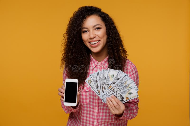 Portrait of an excited young african woman holding bunch of money banknotes and looking at mobile phone over royalty free stock photo