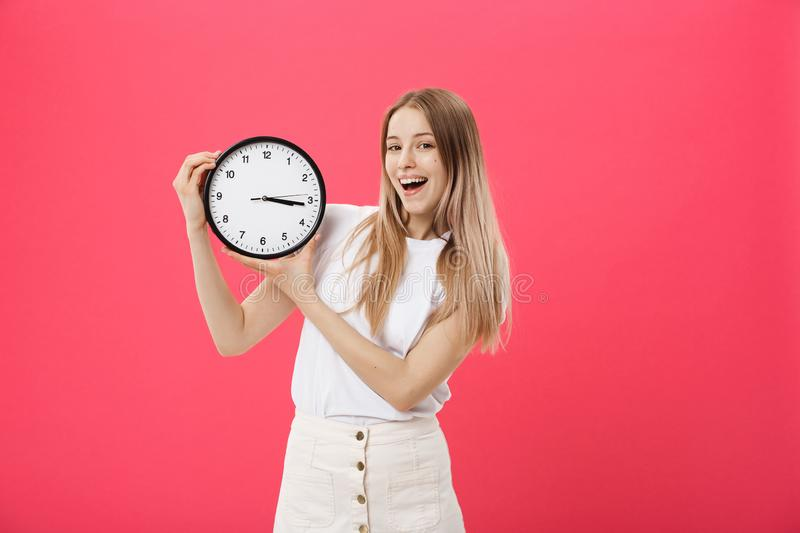 Portrait of an excited young girl dressed in white t-shirt pointing at alarm clock and looking at camera over. Pink background royalty free stock photo
