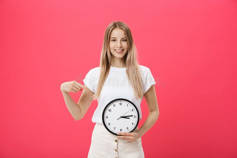 Portrait of an excited young girl dressed in white t-shirt pointing at alarm clock and looking at camera over. Pink background stock photo