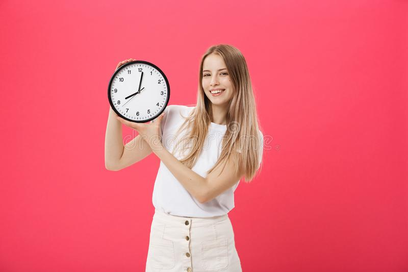 Portrait of an excited young girl dressed in white t-shirt pointing at alarm clock and looking at camera isolated over. Pink background royalty free stock images