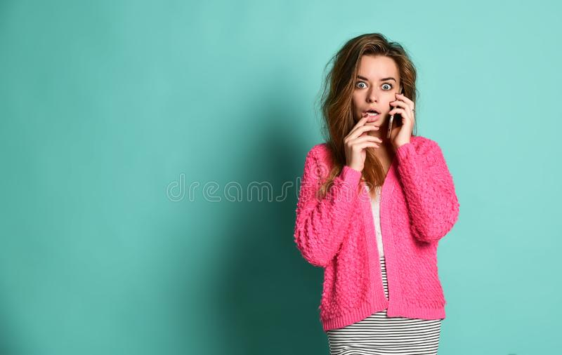 Portrait of an excited young girl standing isolated over violet background, speaking on mobile phone stock photo