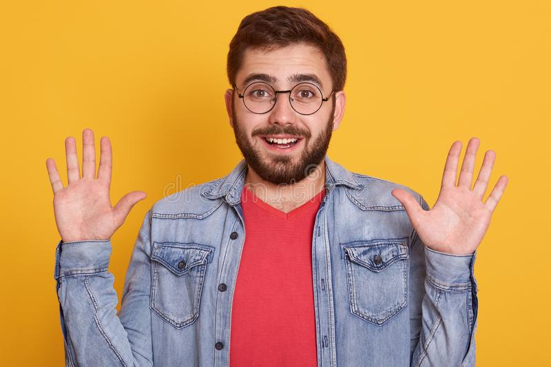 Portrait of excited young guy looking at camera with astonished expression and raising arms, male dressed red shirt and denim stock image