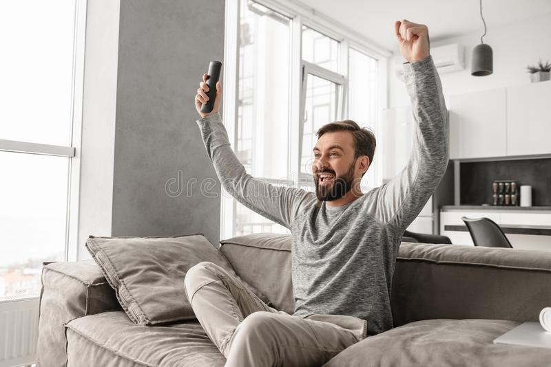Portrait of an excited young man holding TV remote control stock photos