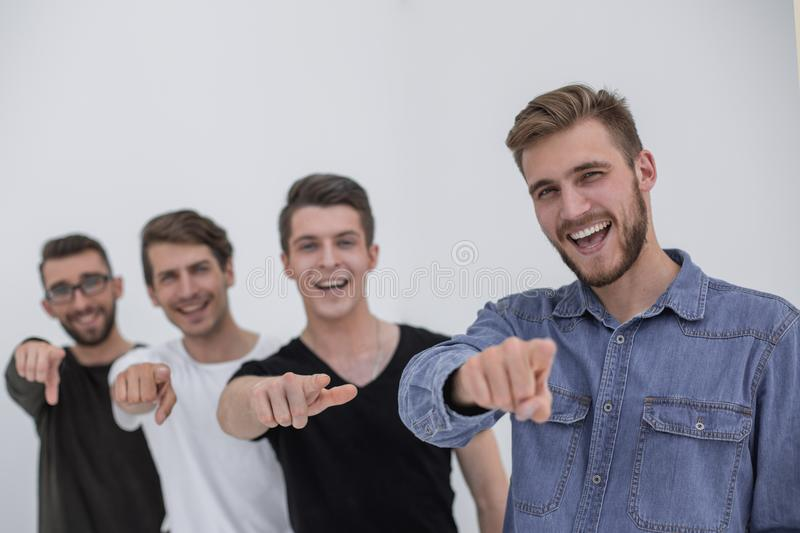 Young group of cheerful students pointing at you. stock photo