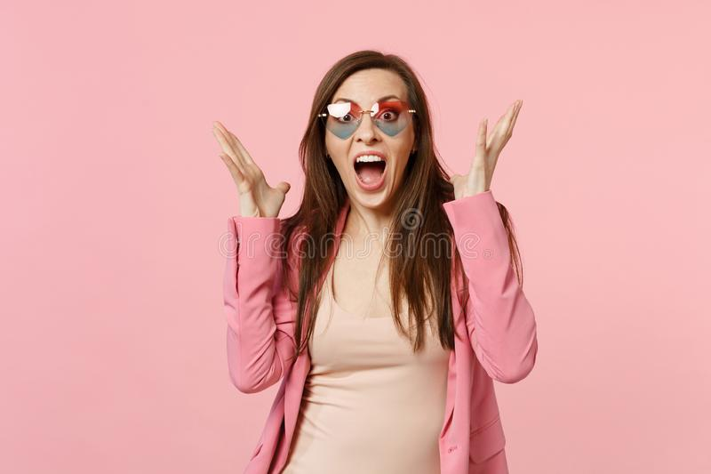 Portrait of excited young woman in heart glasses keeping mouth wide open, spreading hands  on pastel pink royalty free stock photo