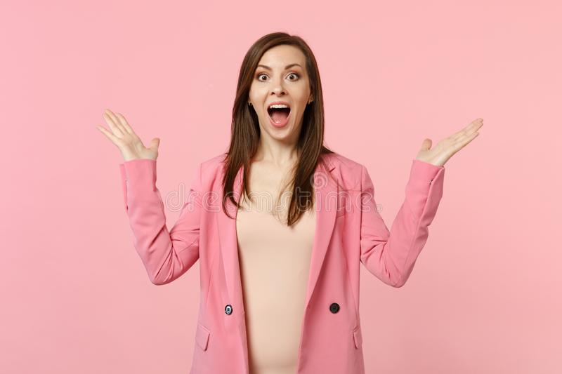 Portrait of excited young woman in jacket keeping mouth wide open, spreading hands isolated on pastel pink wall royalty free stock photo