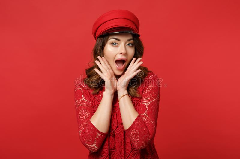 Portrait of excited young woman in lace dress, cap looking camera, holding hands near face isolated on red wall royalty free stock images
