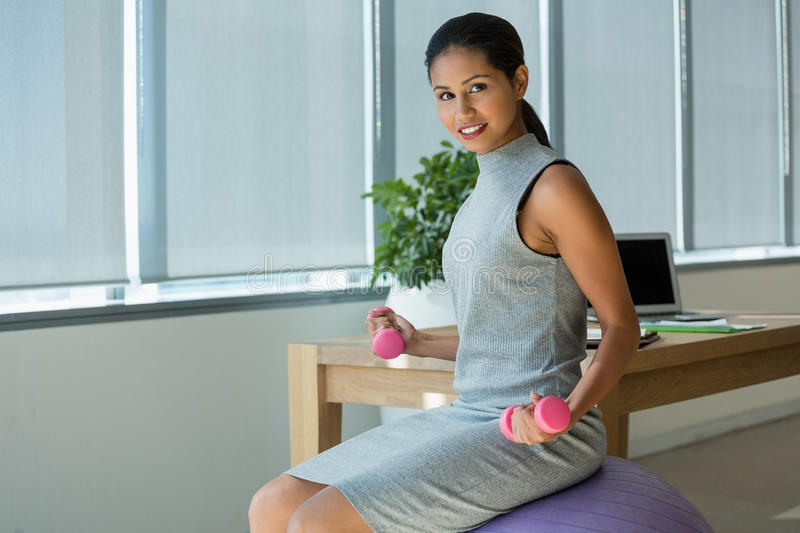 Portrait of executive lifting dumbbells while exercising on fitness ball. In office stock photo