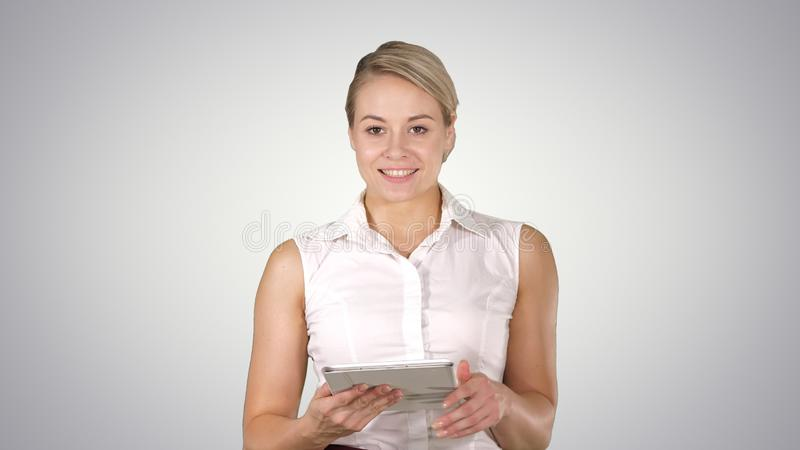 Portrait of an executive professional mature businesswoman holding tablet and talking to the camera on gradient stock photo