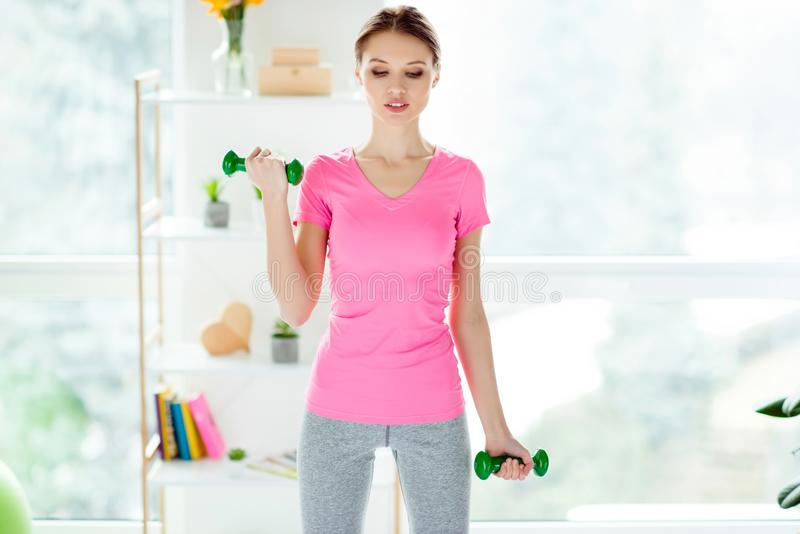 Portrait of exhausted tired strong purposeful attractive focused. Confident self-assured charming woman clothed in sportive outfit doing exercises holding green stock photo