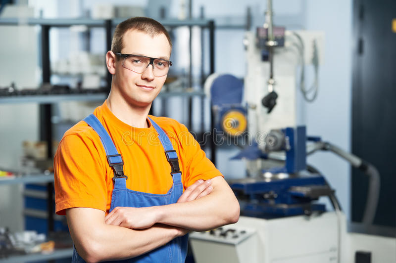 Portrait of experienced industrial worker. Portrait of young adult experienced industrial worker over industry machinery production line manufacturing workshop stock photos