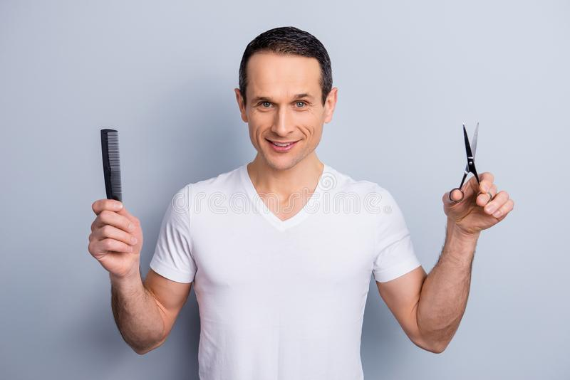 Portrait of experienced, neat, brunet hair expert, stylist having scissors and comb in arms, looking at camera, wearing white stock photography