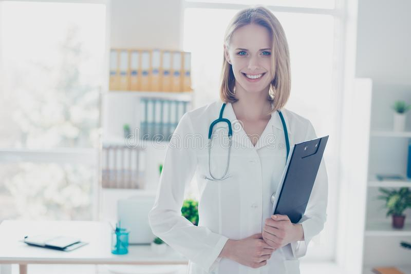 Portrait of experienced qualified confident smiling doctor wearing formal coat, she is holding clipboard, standing against her royalty free stock images